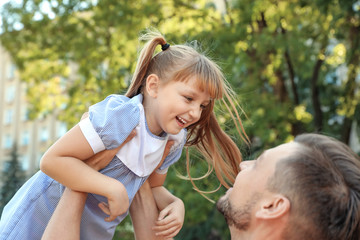 Father having fun with his cute child in green park on sunny day. Happy family