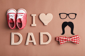 Flat lay composition with baby shoes and bow tie on color background. Happy Father's Day