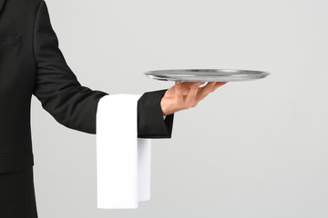 Waiter holding metal tray on light background