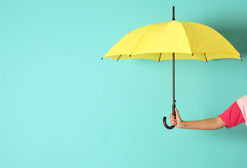 Woman holding beautiful umbrella on color background with space for design