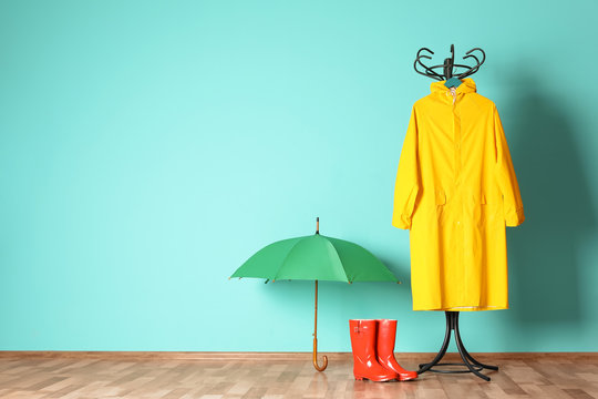 Umbrella, rain coat and boots near color wall with space for design