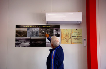 Track manager Gordon Sweeney points to old photographs showing the Mallala Motor Sport Track being used as an aerodrome during World War II, located on the outskirts of the town of Mallala, north of Adelaide