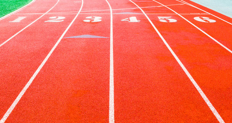 starting line on an empty stadium running track with 6 numbered lanes