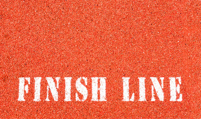the words 'Finish Line' painted in white letters on a stadium running track with copy space