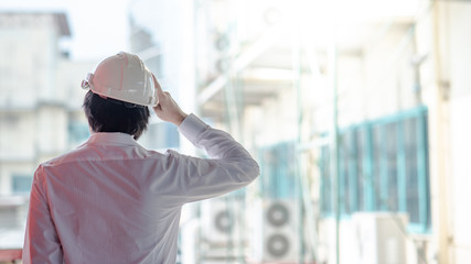 Asian male engineer or architect wearing protective safety helmet at construction site. Engineering, Architecture and building construction concepts