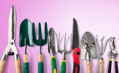 Row of gardening tools on soil background