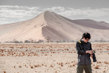 Young male traveler and photographer looking at photo display on camera in Namib desert with sand dune in the background. Travel Namibia, Africa. Photography concept