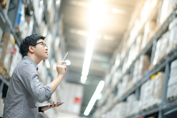 Young Asian man worker doing stocktaking of product in cardboard box on shelves in warehouse by using digital tablet and pen. Physical inventory count concept Wall mural