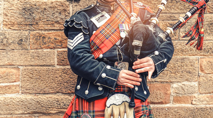 EDINBURGH, SCOTLAND, 24 March 2018 , Scottish bagpiper dressed in traditional red and black tartan dress stand before stone wall. Edinburgh, the most popular tourist city destination in Scotland. Wall mural