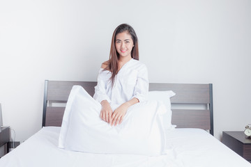Beautiful Asian woman sitting at the end of the bed.