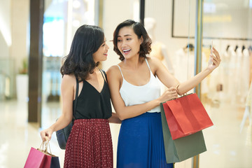 Happy young woman with shopping-bags taking selfie
