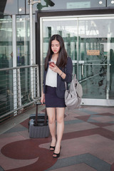 Asia businesswoman on commute transit talking on the smartphone while walking with hand luggage in Airport.
