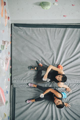 Young climbers resting on mat after climbing, view from above