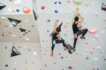 Couple enjoying climbing on artificial wall in gym