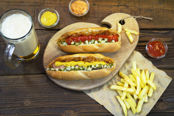 Hot dog and French fries on a wooden table. Fast food. Close up