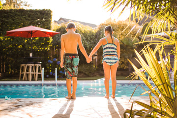 a boy and a girl holding hands, looking into the deep end of the pool together