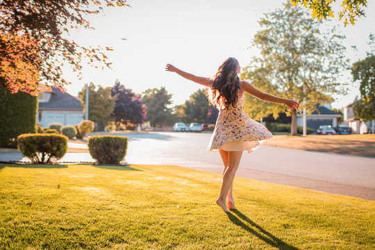 a woman in a dress twirling on a suburban front lawn in the summer at golden hour