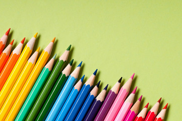 Color pencils isolated on green background.