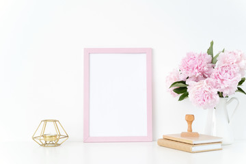 Pink summer portrait frame mock up with a pink peonies, candle and stamp beside the frame, overlay your quote, promotion, headline, or design, great for small businesses, lifestyle bloggers and social