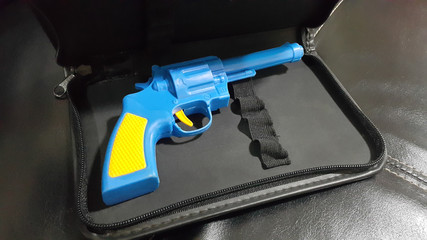 Blue plastic gun A yellow handle and trigger is placed in the black leather case.