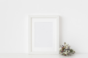 Minimal white a5 portrait frame mockup with small bouquet of dried flowers on white wall background. Empty frame, poster mock up for presentation design. Template frame for text, lettering, modern art