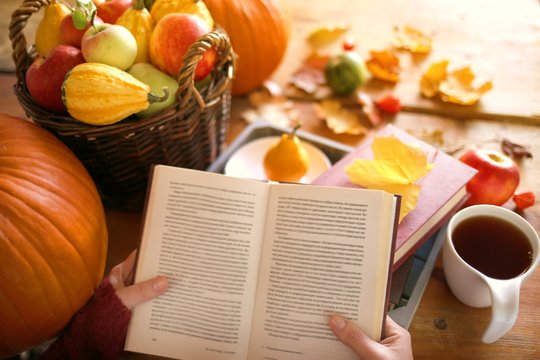 Reading in the autumn day.Autumn books.Autumn reading. book and tea,pumpkin, basket with apples, physalis, yellow maple leaves on a wooden table.Cozy autumn mood
