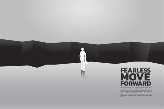 silhouette of businessman with briefcase step forward to abyss. concept of business challenge and courage man