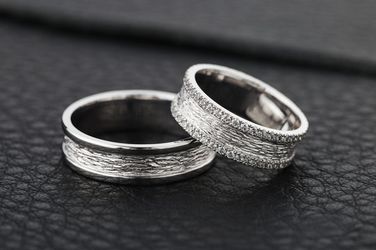 Two silver wedding rings on black leather background