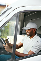 Courier. Delivery Man Reading Addresses Sitting In Delivery Van