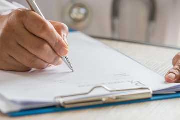 Healthcare medical concept, Hands Doctor's writing and working on prescription clipboard with record information paper folders on desk in hospital or clinic. Selective focus