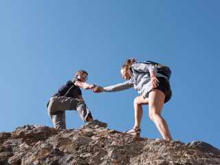 Helping hand couple hikers in mountains