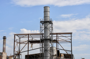 Sugar factory under construction, metal chimney with platforms and other elements of construction, another pipe and equipment in the background