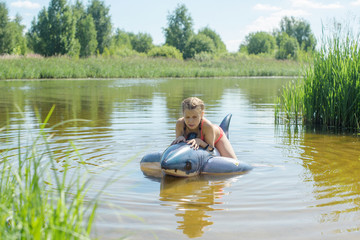 girl swimming in the river on an inflatable shark