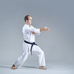 Young athlete doing formal karate exercises on a gray background