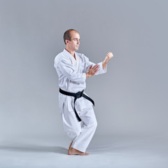 A man in a low rack coaches a formal karate exercise