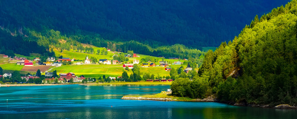 Norwegian village banner landscape with fjord, mountains and colorful houses, church in Olden, Norway