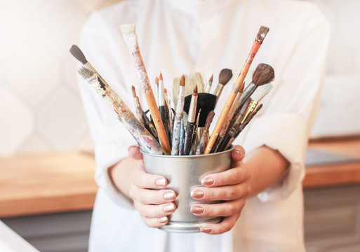 Different brushes in metal bucket with artist hands, selective focus