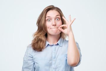 Woman zipping her mouth shut - keeping quiet concept