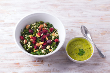Warm kale salad with brown rice, dried cranberries and nuts on a light background. Delicious healthy diet food