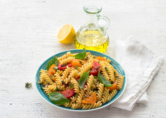 Summer pasta with tomatoes, herbs and olive oil on a light background. Delicious healthy diet