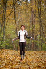 Photo of sporty woman jumping with rope at autumn forest