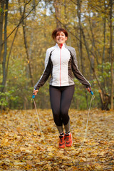Image of sporty woman jumping with rope at autumn forest