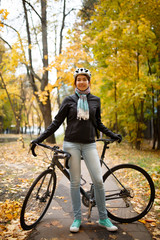 Photo of woman in helmet, jeans next to bicycle