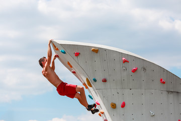 Photo of young sporty man in red shorts practicing on wall for rock climbing against blue sky with clouds