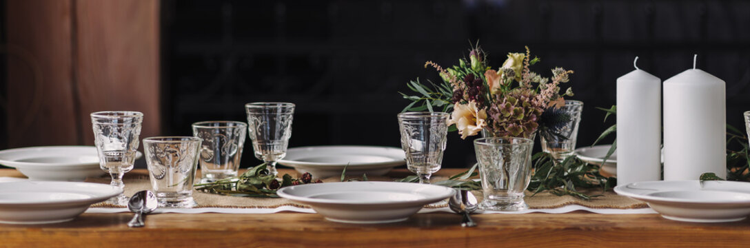 Panorama of noble lifestyle table decoration for thanksgiving dinner, precious glasses, floral decor, white candles, autumnal flowers, white porcelain on a long wooden table. Still life dinner