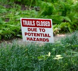 A red and white trail closed sign on a close up view.
