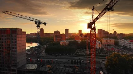 Fotobehang - Aerial view of construction cranes silhouettes against sunset sky background. 4K UHD.