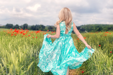 Little girl running away in a field whith poppy outdoors