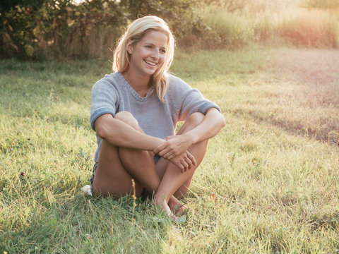 Blonde woman sitting outdoor at sunset