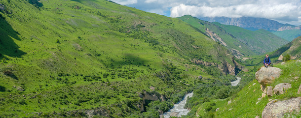 A girl with a backpack is resting in the mountains. Panorama of the Caucasus Mountains.